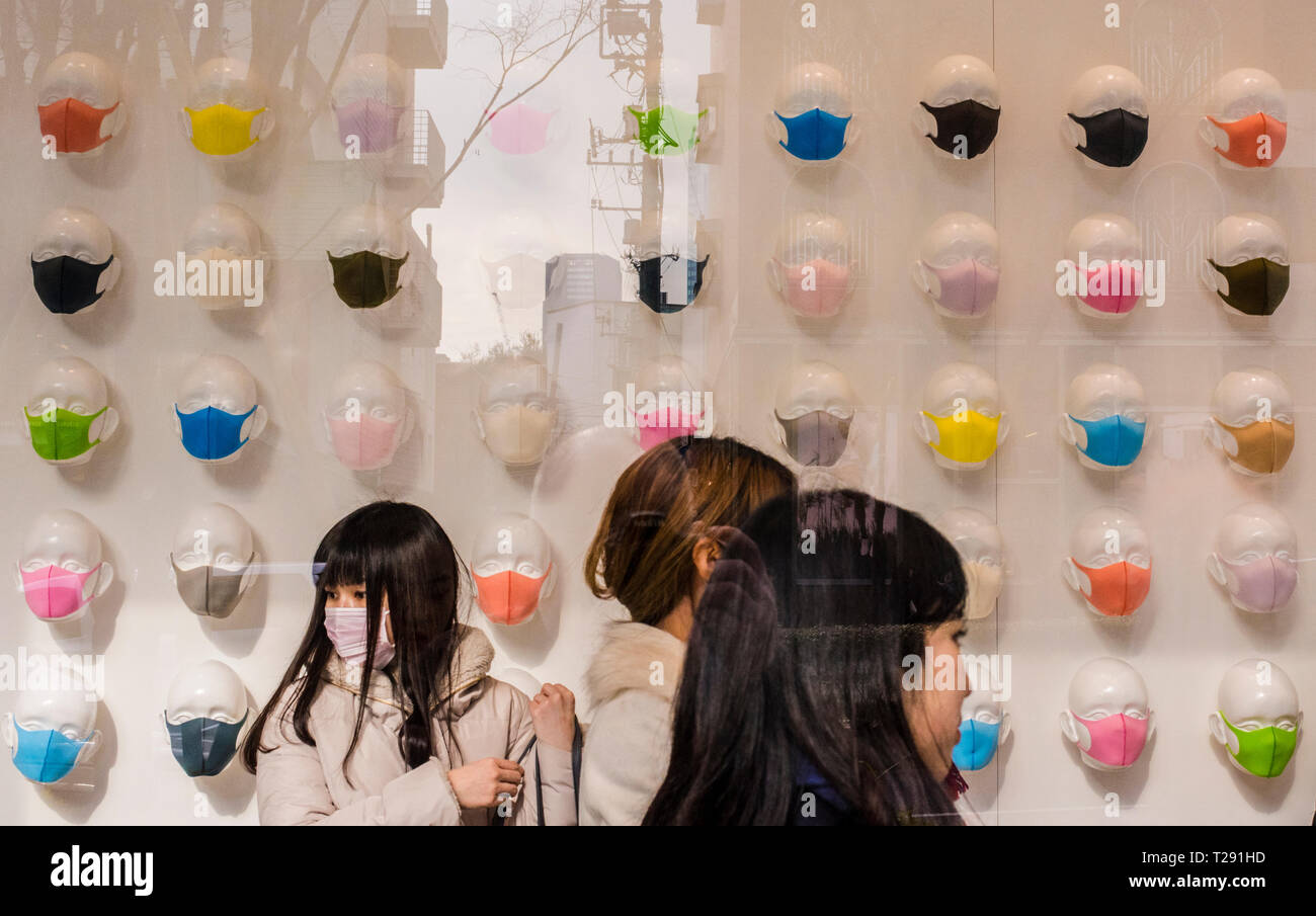 Three women in shop, seen through window, with large  selection of colourful pollution masks on display, Omotesando Area, Tokyo, Japan - Stock Image