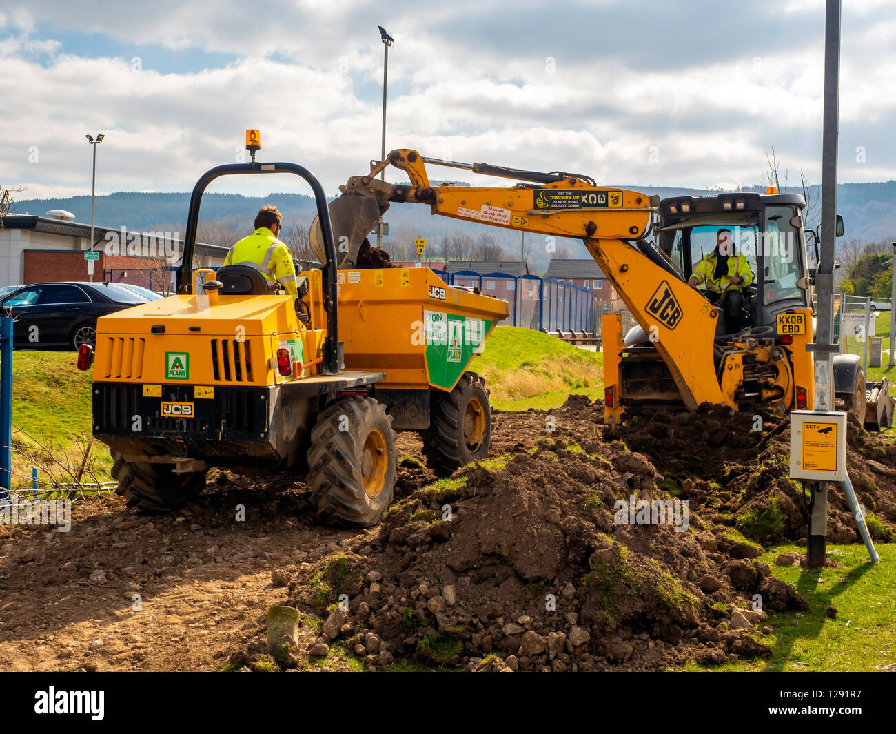 Workmen using a JCB 3CX excavator loading excavated topsoil into a dumper truck for removal Stock Photo