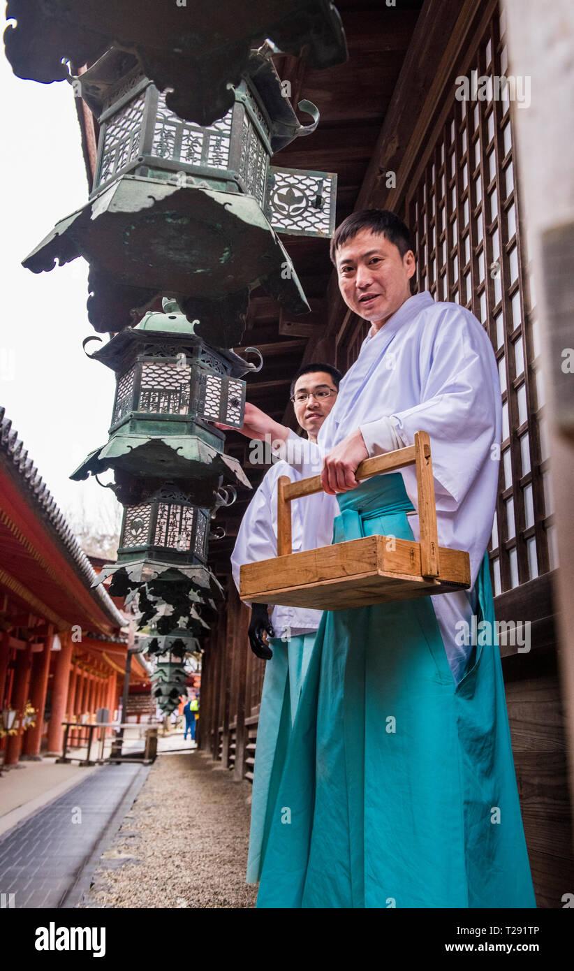 Portrait of monks, switching on lanterns, Kasuga-taisha shrine, Nara, Japan, low angle view - Stock Image
