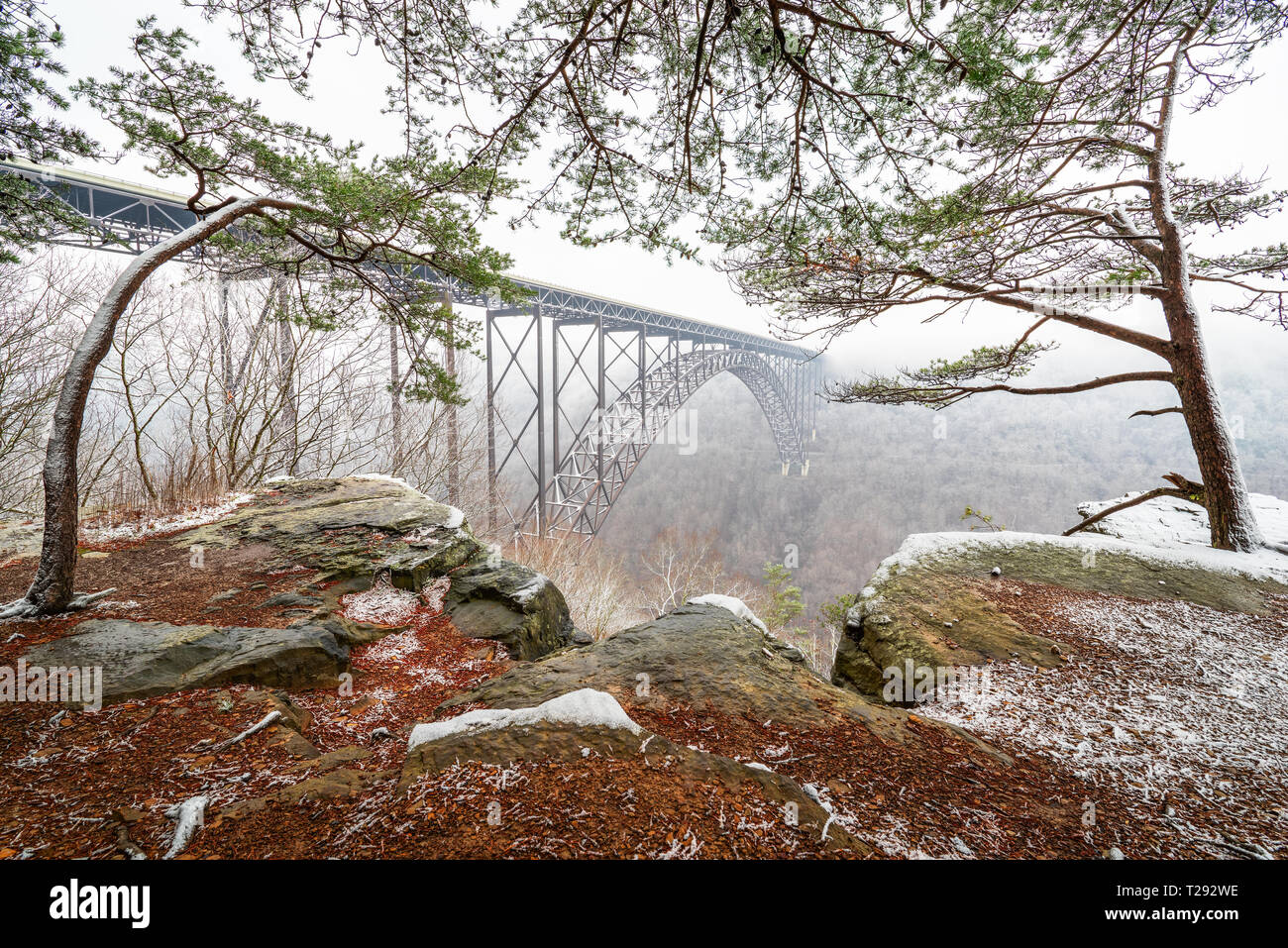 The expansive New River Gorge Bridge of West Virginia appears to nearly float in the foggy air viewed through a window of snow dusted rock and pine. - Stock Image