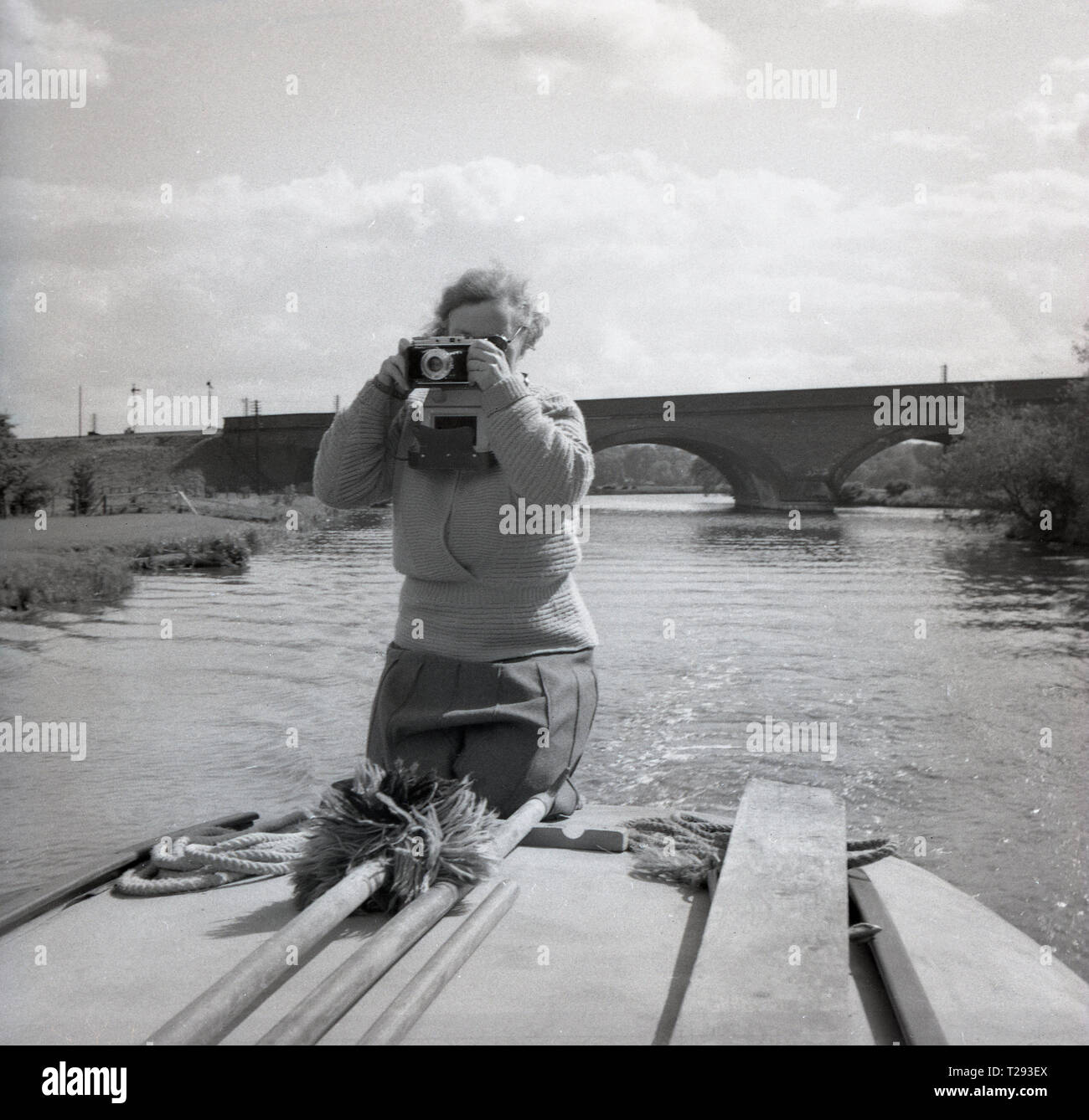 1950s, lady kneeling on the back of a motor boat or motor launch with a film camera taking a photograph, Oxford, England, UK. - Stock Image