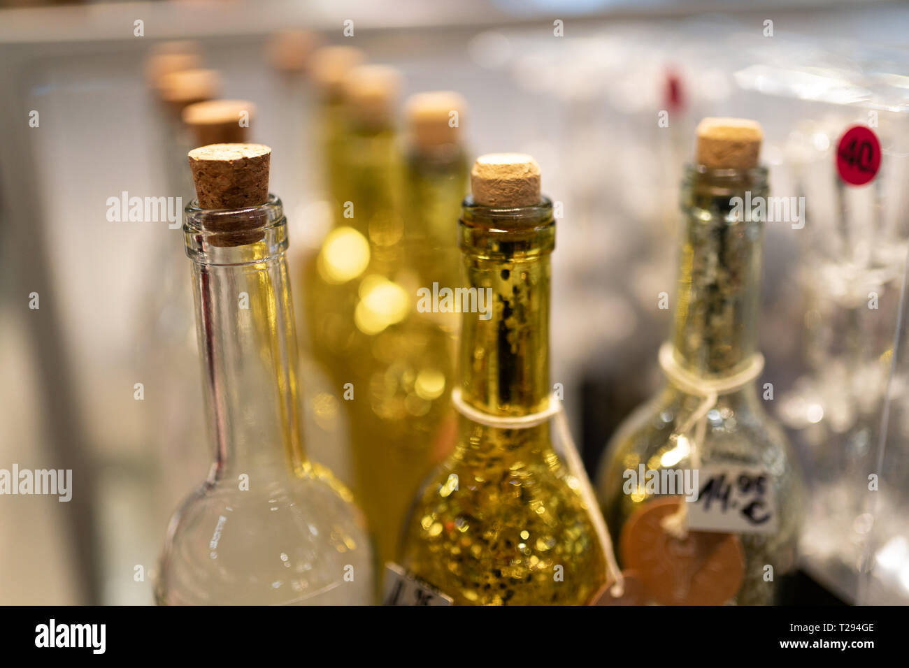 Yellow and white glass bottles in a shop - Stock Image