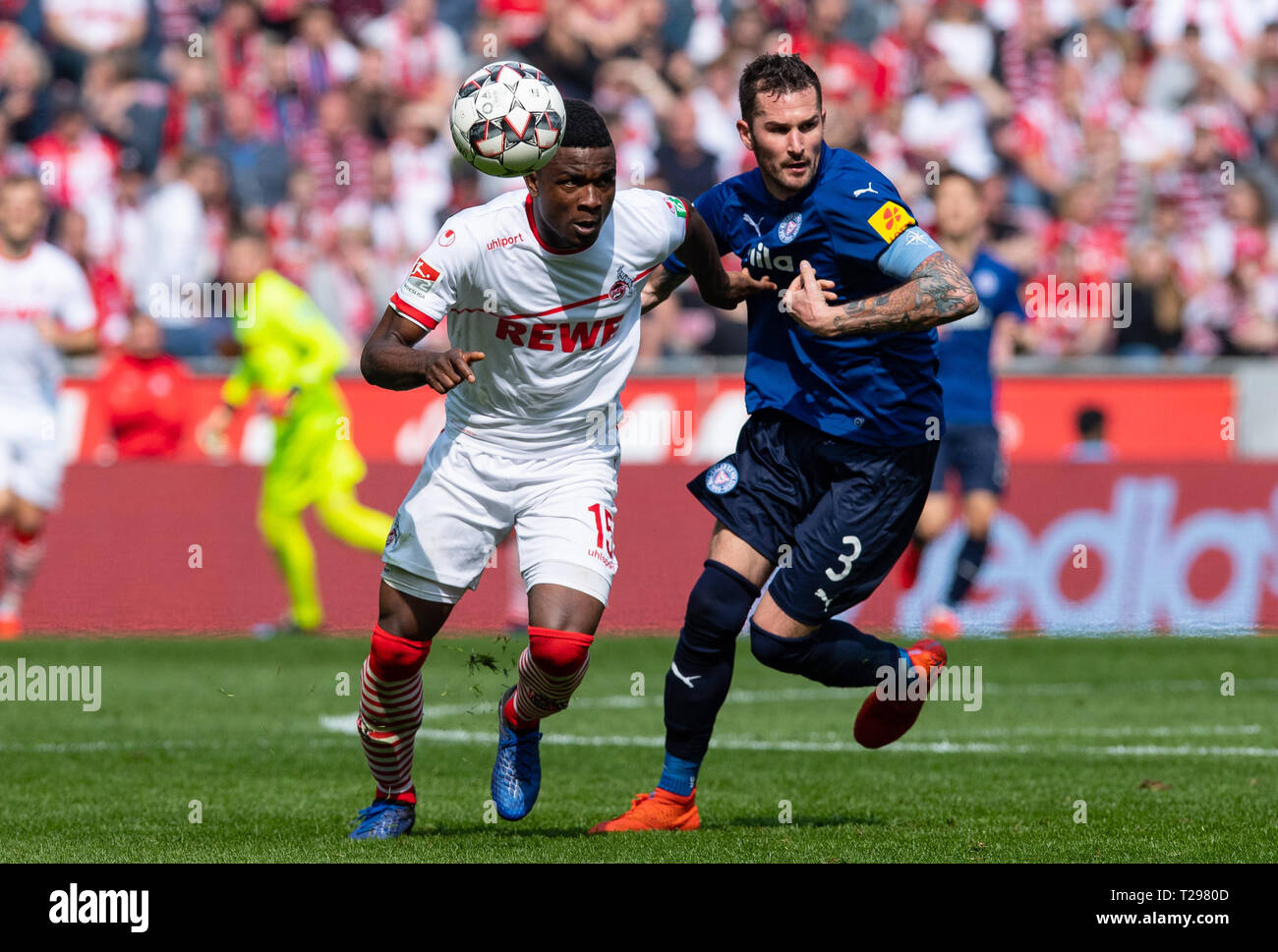 Cologne, Germany. 31st Mar, 2019.  Soccer: 2nd Bundesliga, 1st FC Cologne - Holstein Kiel, 27th matchday in the Rhein-Energie-Stadion. Cologne's Jhon Cordoba (l) and Kiel's Dominik Schmidt fight for the ball. Photo: Guido Kirchner/dpa - IMPORTANT NOTE: In accordance with the requirements of the DFL Deutsche Fußball Liga or the DFB Deutscher Fußball-Bund, it is prohibited to use or have used photographs taken in the stadium and/or the match in the form of sequence images and/or video-like photo sequences. Credit: dpa picture alliance/Alamy Live News Stock Photo