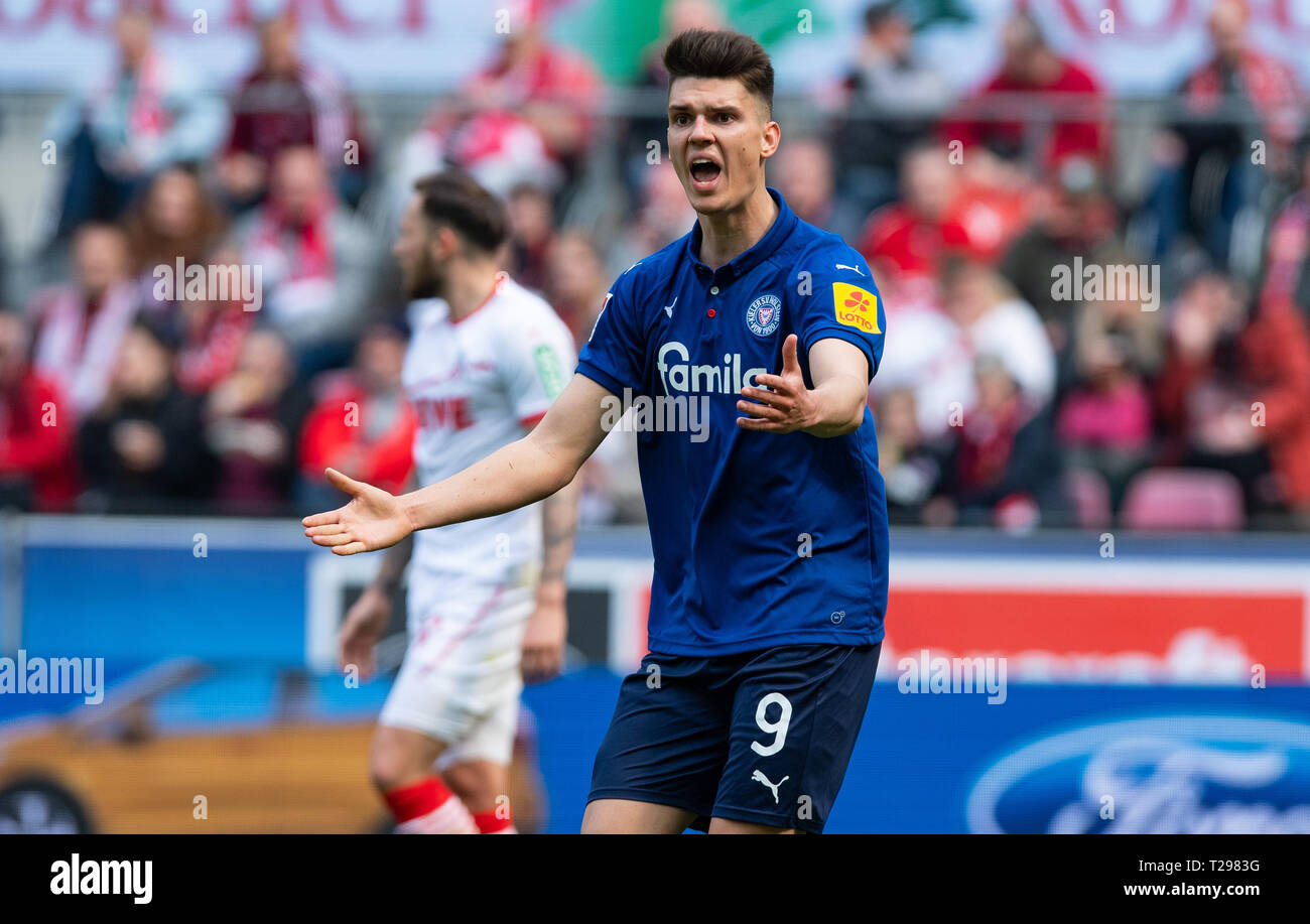 Cologne, Germany. 31st Mar, 2019.  Soccer: 2nd Bundesliga, 1st FC Cologne - Holstein Kiel, 27th matchday in the Rhein-Energie-Stadion. Kiel's Mathias Honsak stands on the square with his arms outstretched. Photo: Guido Kirchner/dpa - IMPORTANT NOTE: In accordance with the requirements of the DFL Deutsche Fußball Liga or the DFB Deutscher Fußball-Bund, it is prohibited to use or have used photographs taken in the stadium and/or the match in the form of sequence images and/or video-like photo sequences. Credit: dpa picture alliance/Alamy Live News Stock Photo