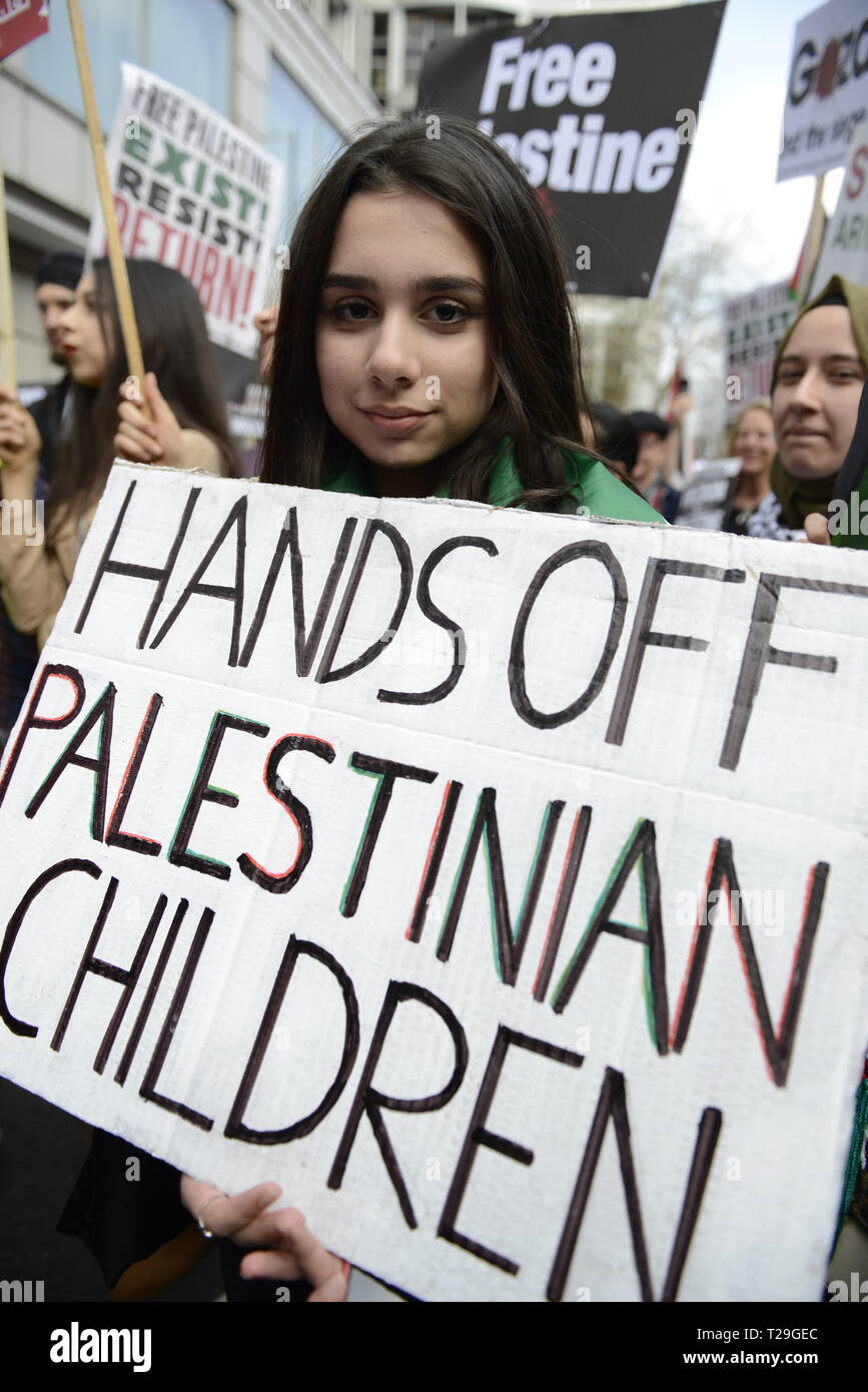 A protester is seen holding a placard that says Hands off Palestinian children during the Exist, Resist, Return Rally for Palestine in London. People gather outside the Israeli embassy in London to demonstrate against the Israeli government, and to demand respect for Palestinians' fundamental rights to exist, resist and return. Palestinians are calling for global protests to support their right to come back to their villages. Rally was organized by Palestine Solidarity Campaign, Stop the War Coalition, Palestinian Forum in Britain, Friends of Al- Aqsa, and Muslim Association of Britain. - Stock Image