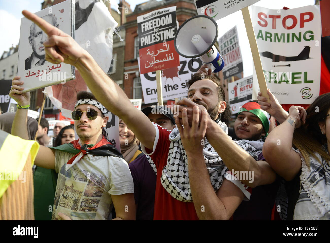 A protester is seen shouting slogans on a megaphone during the Exist, Resist, Return Rally for Palestine in London. People gather outside the Israeli embassy in London to demonstrate against the Israeli government, and to demand respect for Palestinians' fundamental rights to exist, resist and return. Palestinians are calling for global protests to support their right to come back to their villages. Rally was organized by Palestine Solidarity Campaign, Stop the War Coalition, Palestinian Forum in Britain, Friends of Al- Aqsa, and Muslim Association of Britain. - Stock Image
