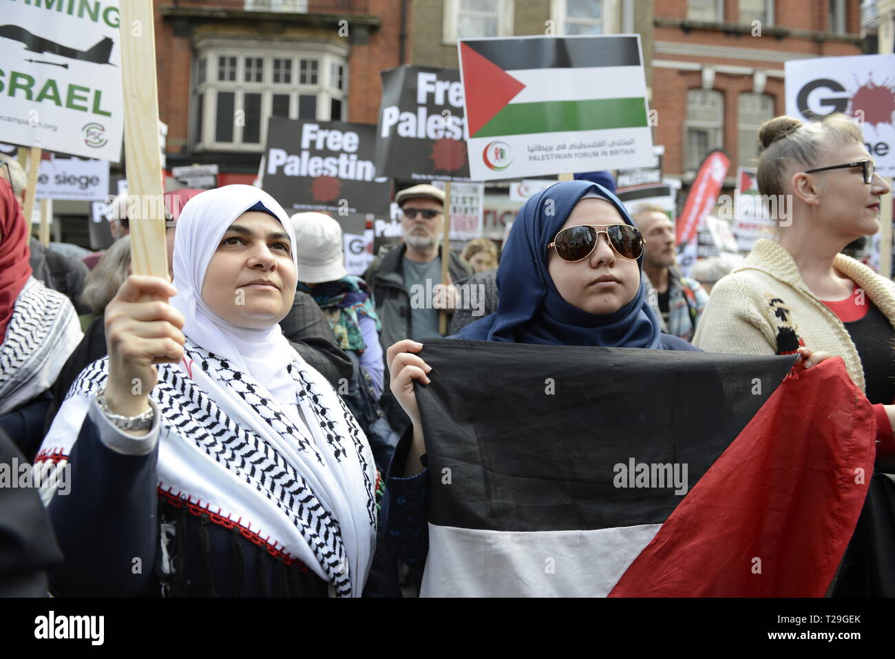 Protesters are seen holding placards and a Palestinian flag during the Exist, Resist, Return Rally for Palestine in London. People gather outside the Israeli embassy in London to demonstrate against the Israeli government, and to demand respect for Palestinians' fundamental rights to exist, resist and return. Palestinians are calling for global protests to support their right to come back to their villages. Rally was organized by Palestine Solidarity Campaign, Stop the War Coalition, Palestinian Forum in Britain, Friends of Al- Aqsa, and Muslim Association of Britain. - Stock Image