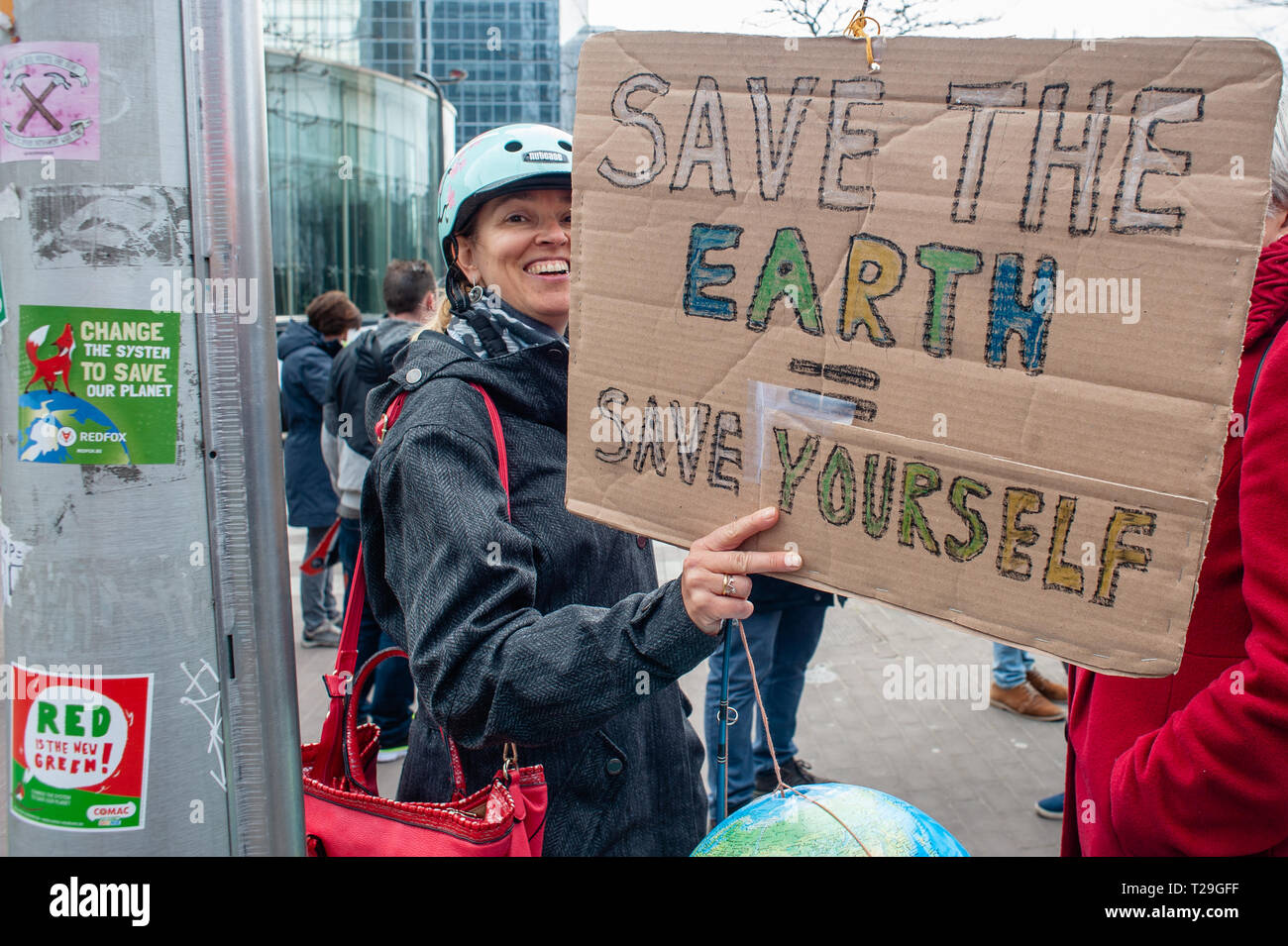 A woman is seen smiling while holding a placard during the demonstration. Thousands of people gathered as always at the Brussels North station to demand a declaration of a state of environmental emergency and a climate law to reduce C02 emissions by 55% by 2030, the climate as a top priority, the adoption of the Finance-Climate Pact, the respect of the Paris agreements and the protection of water and forests. - Stock Image