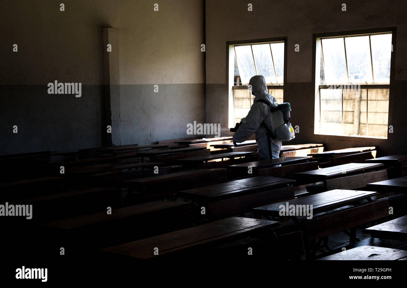 Beira, Mozambique. 29th Mar, 2019. A member of the Chinese rescue team sprays disinfectants at a classroom of June 25 Elementary School in Beira, Mozambique, March 29, 2019. TO GO WITH 'Feature: Chinese rescuers join Mozambicans to prevent epidemics following Idai disaster' Credit: Zhang Yu/Xinhua/Alamy Live News - Stock Image