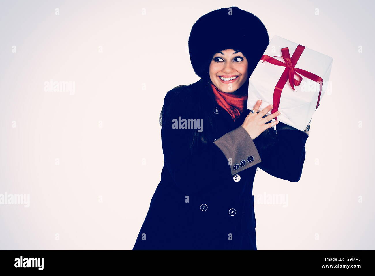 Beautiful woman with a gift in the hands, trying to guess what's in the box - Stock Image