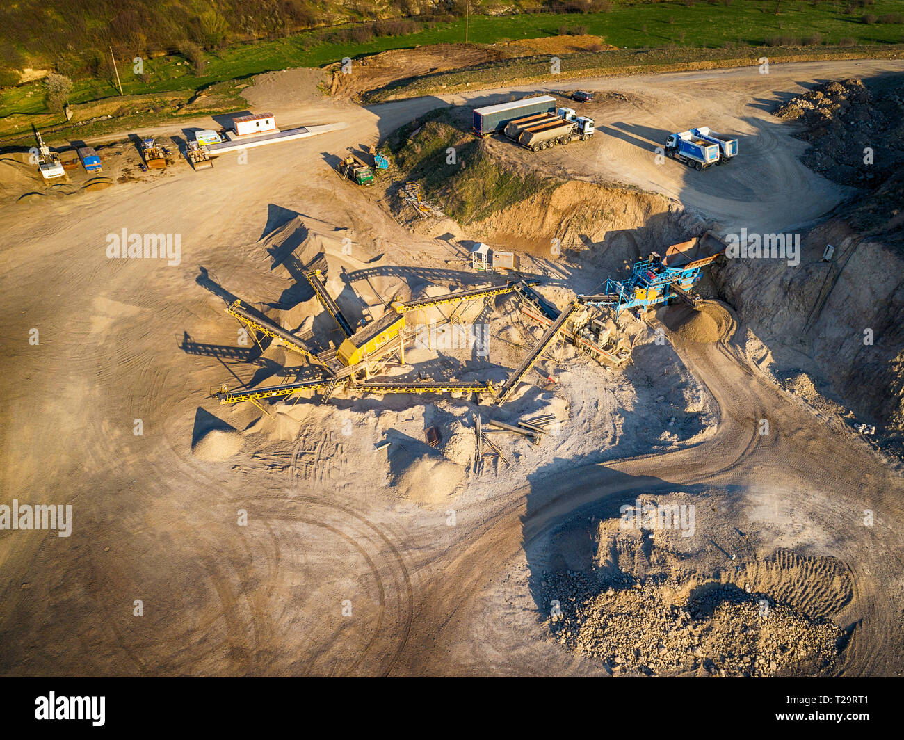 Panoramic view at sunset of gravel quarry,mining of yellow construction gravel, pumping gravel with help of powerful pumps, post-apocalyptic landscapе Stock Photo