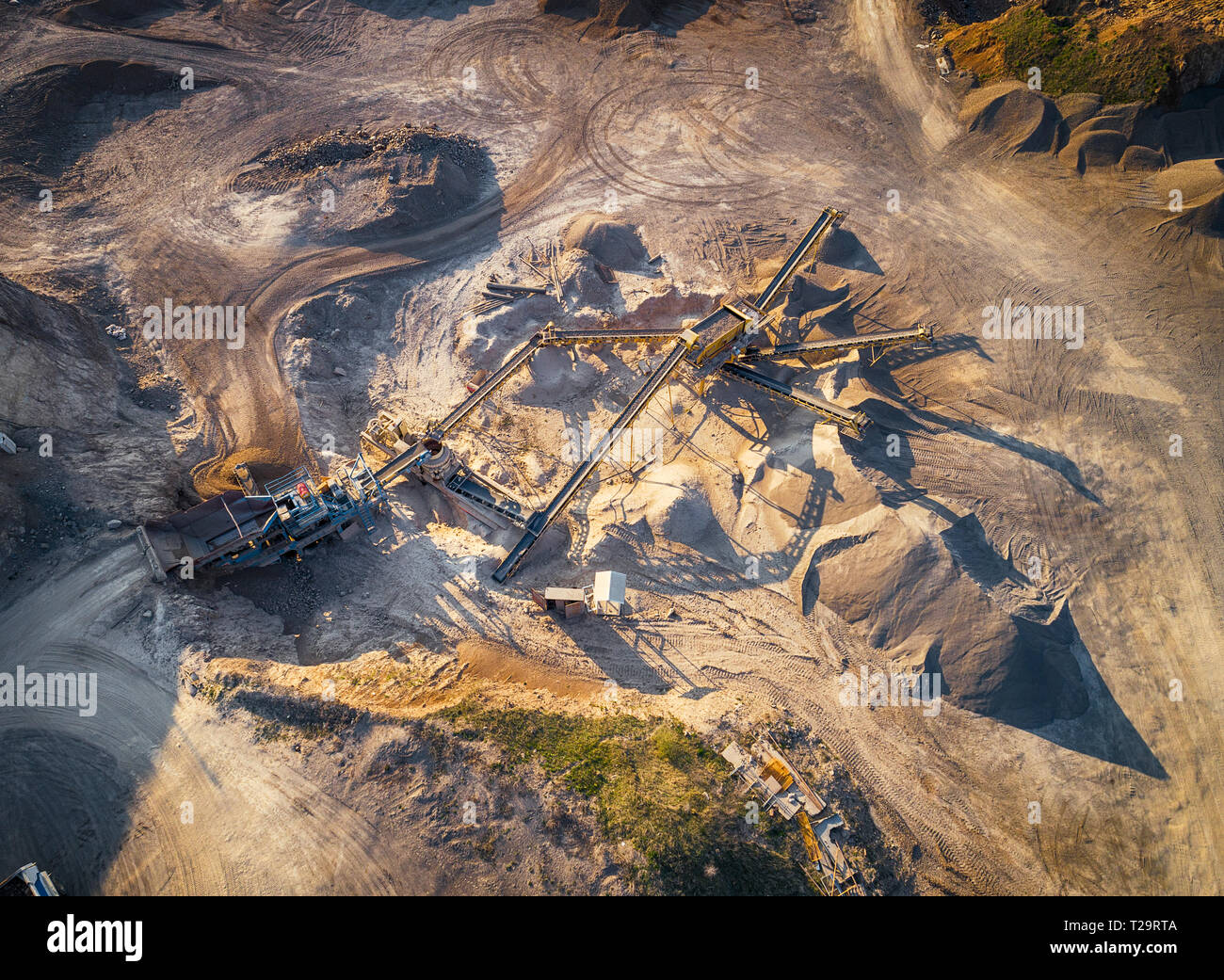 Panoramic view at sunset of gravel quarry,mining of yellow construction gravel, pumping gravel with help of powerful pumps, post-apocalyptic landscapе - Stock Image