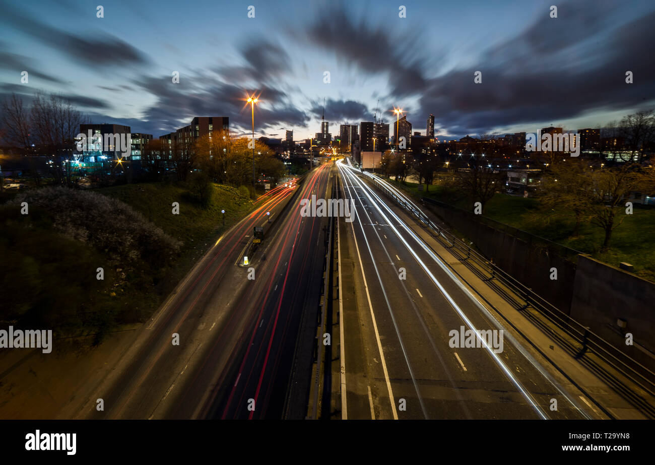 Leeds City skyline with light trails leading to it. - Stock Image