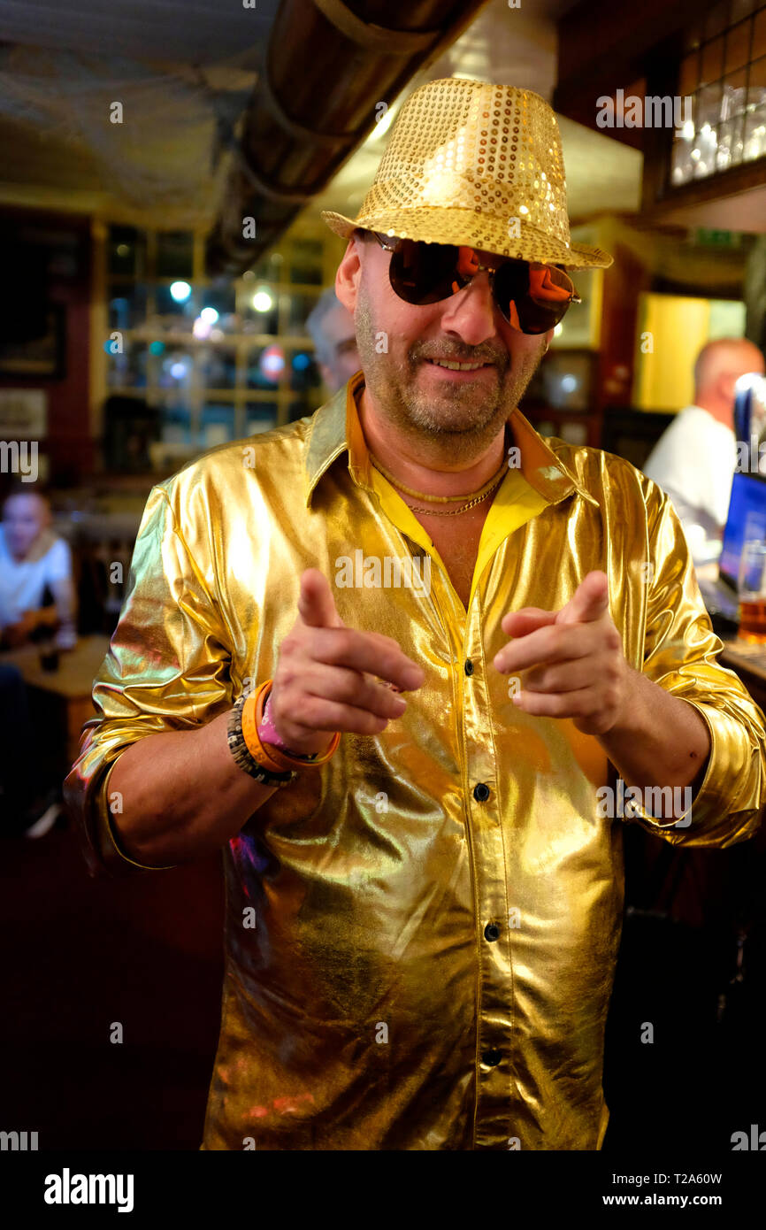 man,in,pub,wearing,gold,suit,hat,sunglasses,pointing,at,camera,pop,festival,Isle of Wight,Newport, UK, Stock Photo