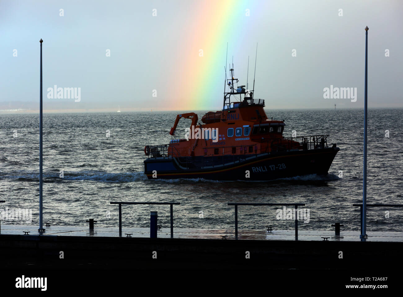 huge,tug,lifeboat,tanker,yacht,large,bright,rainbow,over,sea,Cowes,Isle of Wight,England, - Stock Image