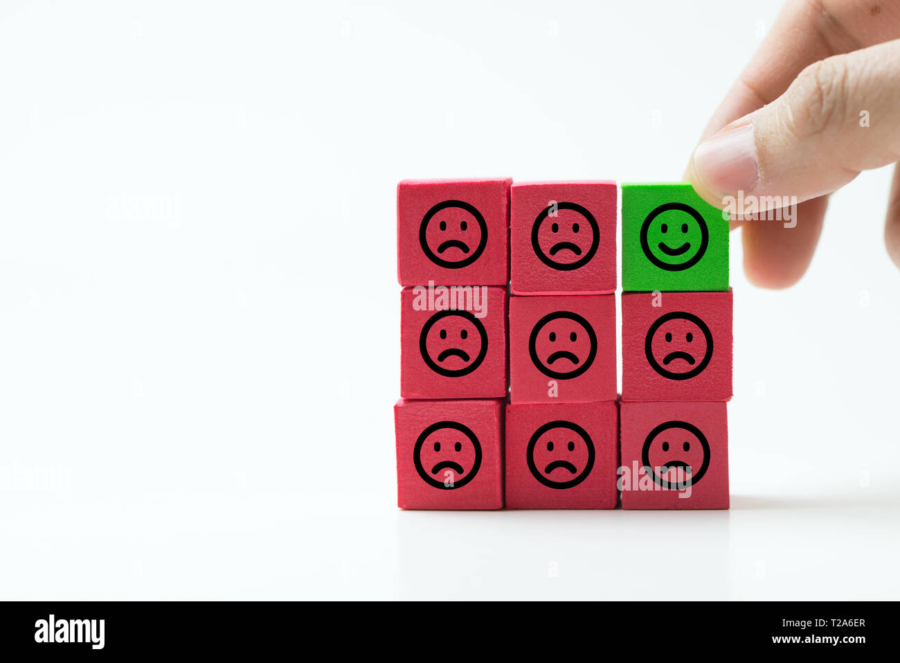 Unique, optimistic, happiness, difference concept using single happy face among many sad faces. - Stock Image