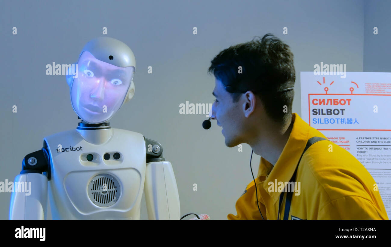 Funny humanoid robot with display face talking with guide man - Stock Image