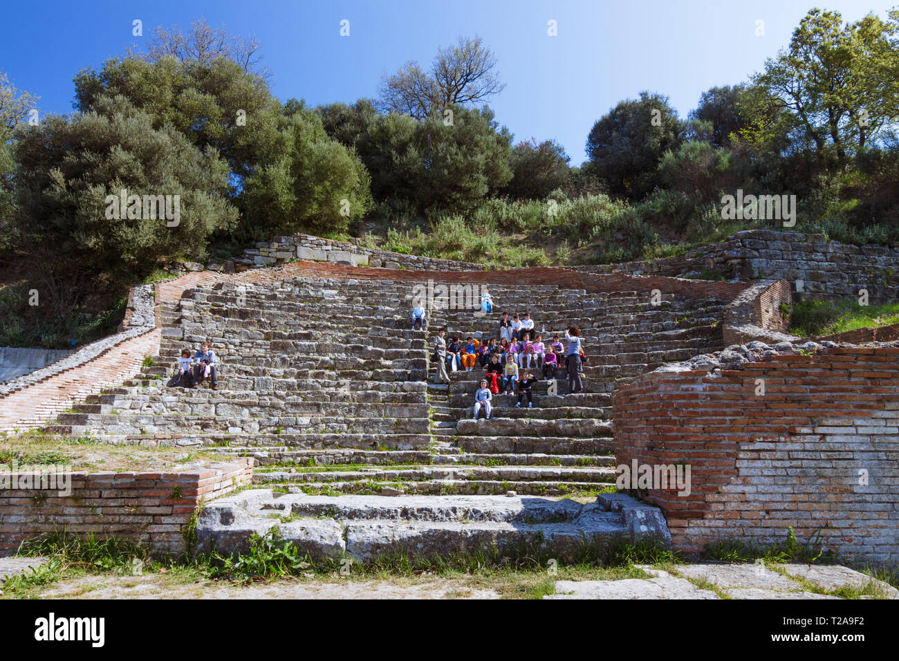 Apollonia, Fier, Albania : A group of teenagers stand at the ruins of the Odeon Theater. Founded by Greeks in 588 BC, Apollonia grew into an important - Stock Image