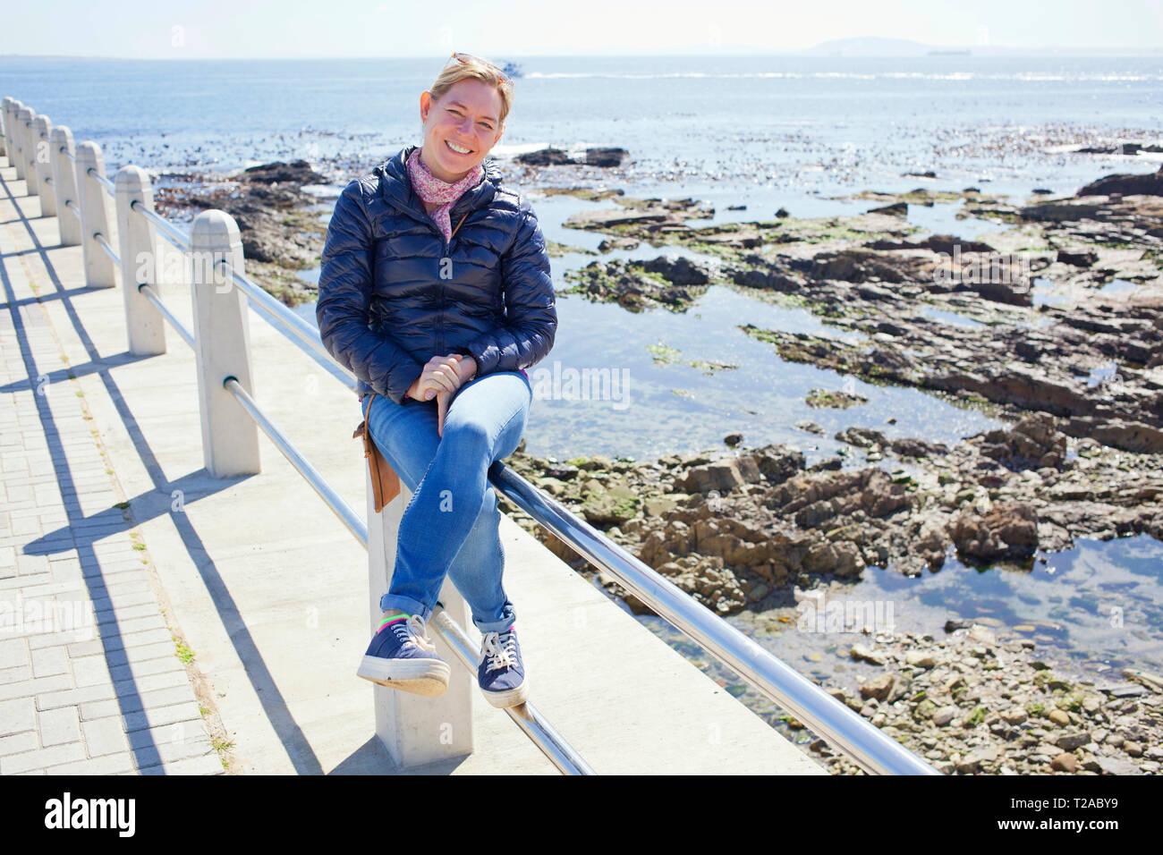 Woman sitting on railing along Sea Point Promenade, Cape Town Stock Photo