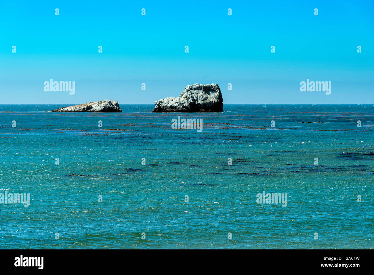 Overlooking ocean with rocky formations in sea under bright blue sky. Stock Photo