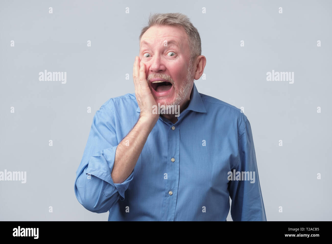 Amazed senior man in blue shirt keeping mouth wide open, put hands on cheeks. People sincere emotions. Studio shoot - Stock Image