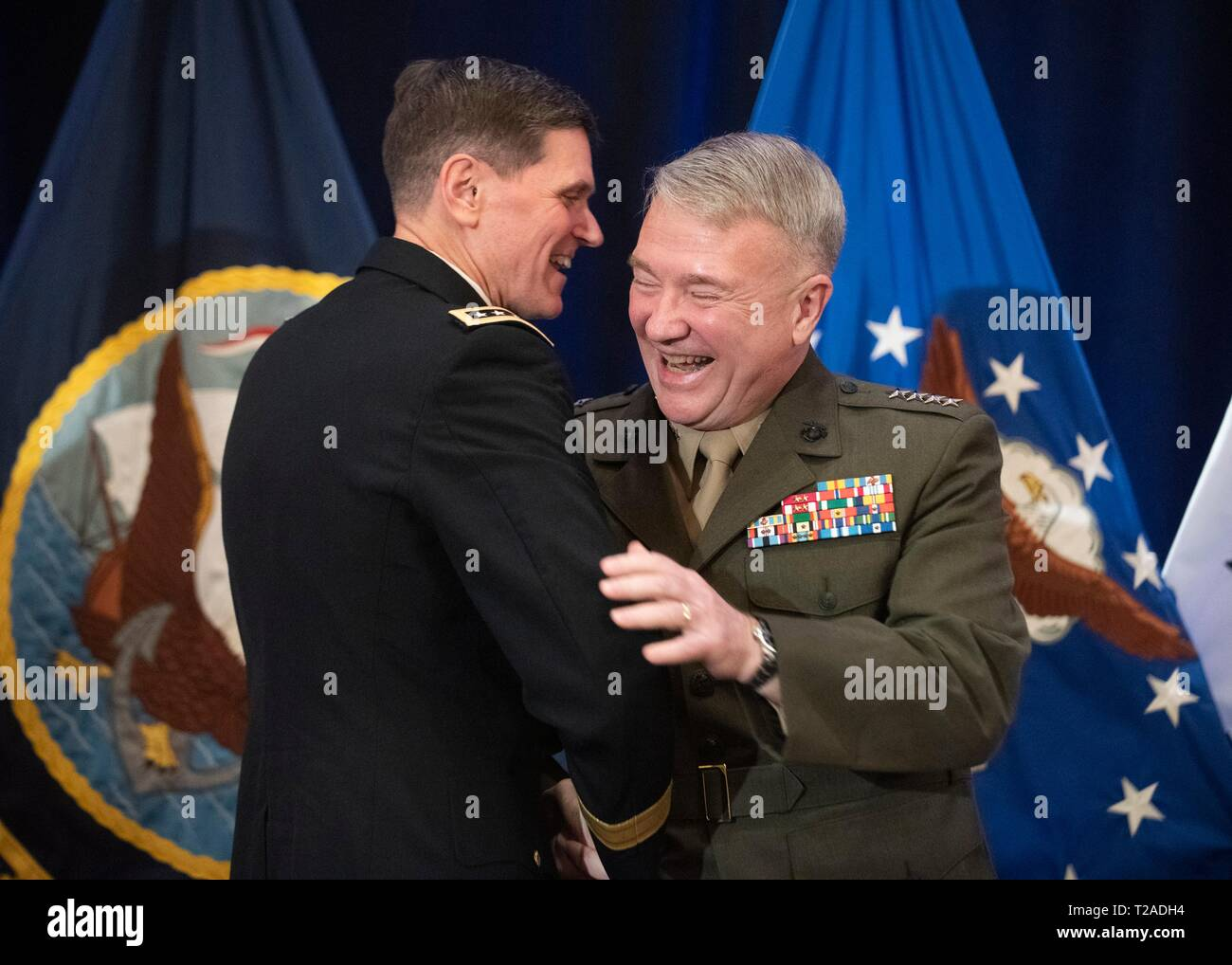The outgoing commander of U.S. Central Command, General Joseph L. Votel, embraces his replacement Marine Corps Gen. Frank McKenzie, right, during his retirement ceremony at Macdill Air Force Base March 29, 2019 in Tampa, Florida. Votel retired after 39 years of military service. Stock Photo