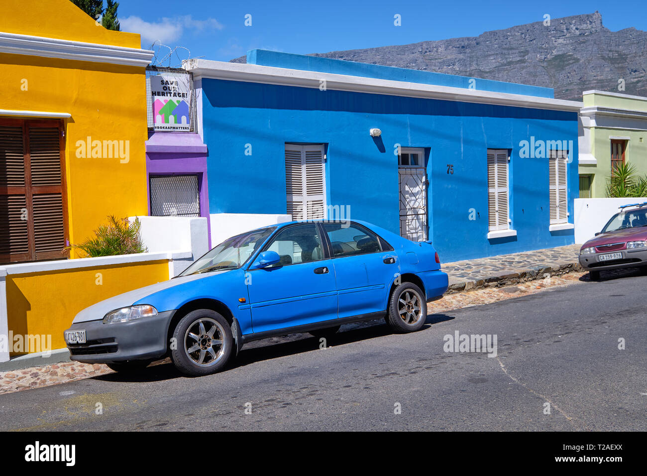 Blue car parked in front of blue house in Bo Kaap, With table Mountain in back. Cape Town, South Africa, March 21, 2019. Stock Photo