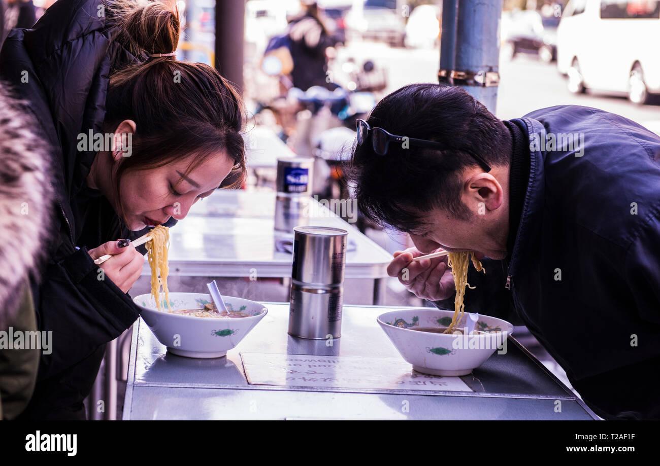 Two people in restaurant, eating bowl of noodles at Tsukiji Fish market, Tokyo, Japan - Stock Image