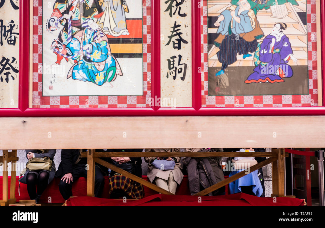 Row of people sitting outside Kabuki-za Theatre, faces obscured by decorative panels outside theatre, Tokyo, Japan - Stock Image