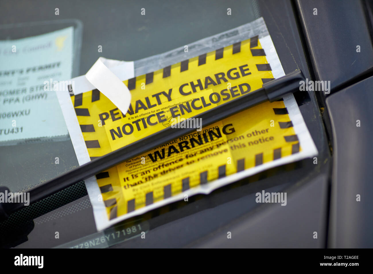 Yellow window sticker Penalty Charge Notice council parking fine attached to car windscreen  by Liverpool, Council - Stock Image