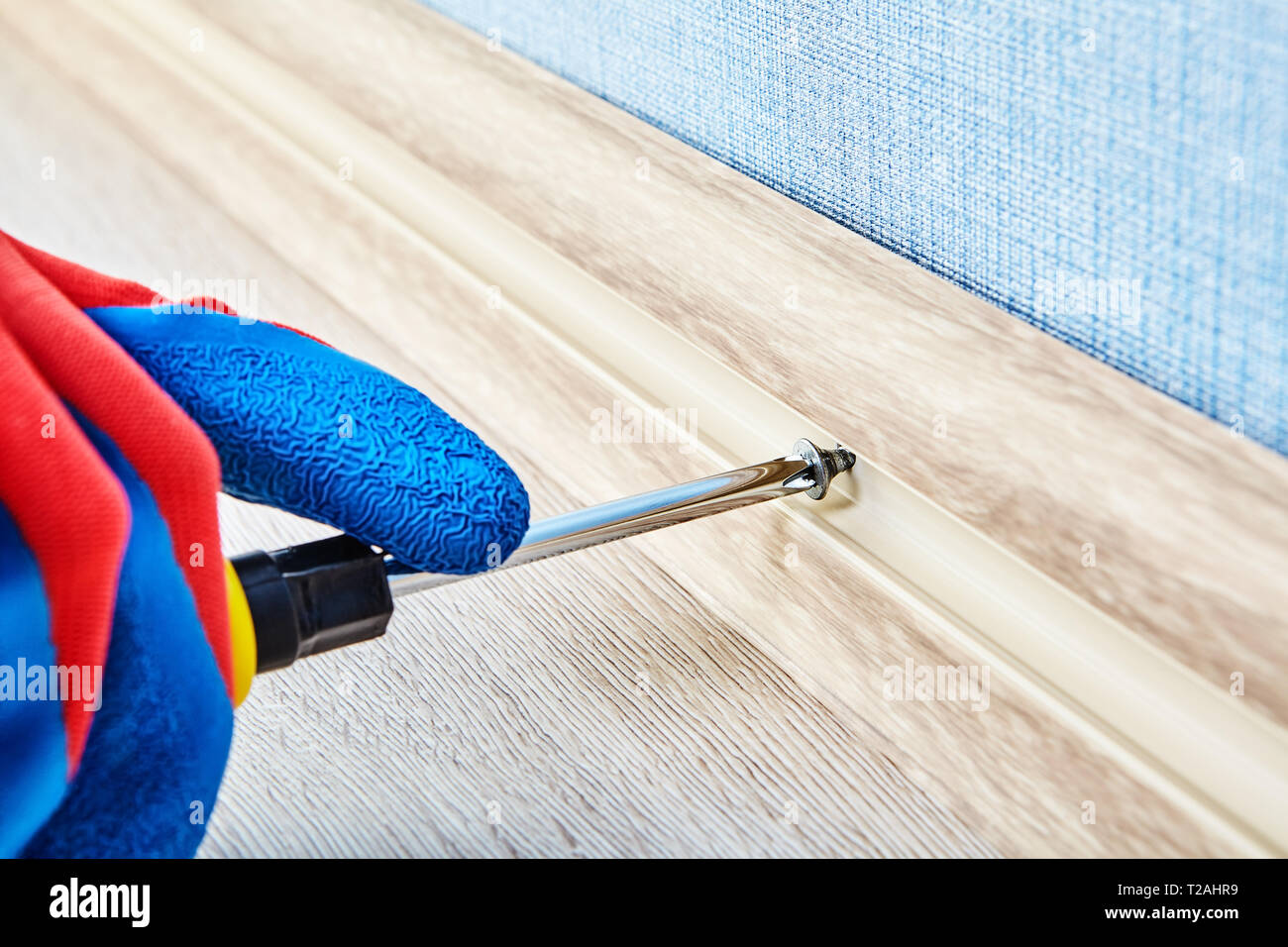 Tightening screw in flexible plinth for the floor with hand tool by electrician, close-up. - Stock Image