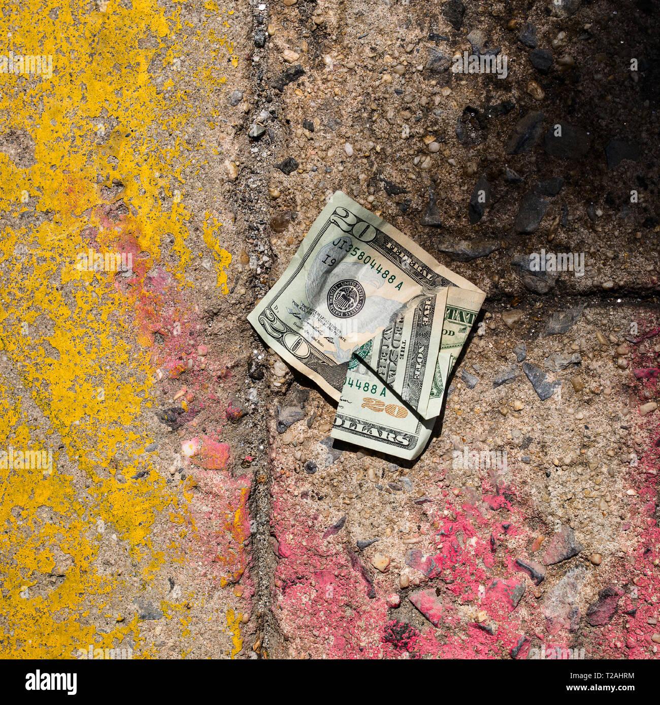 Crumpled money on sidewalk Stock Photo