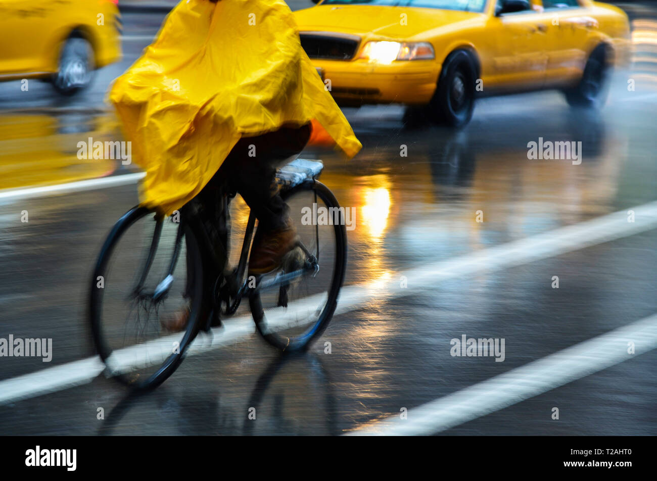 Cyclist in yellow poncho during rain in New York City, USA - Stock Image