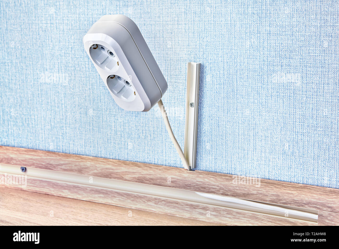 Electrical duplex power plug receptacle in white plastic box. - Stock Image
