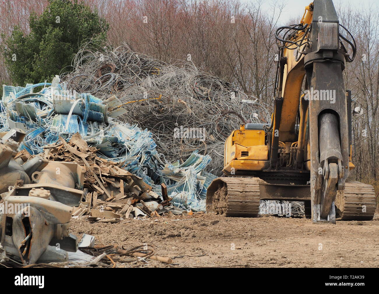 Scrap Yard metal shear mounted on excavator with pile of fiberglass recyclable scrap - Stock Image