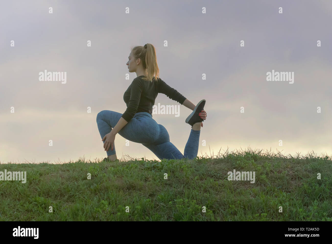 Young Attractive Woman Practicing Yoga, Working Out, Outdoor Morning Workout, Beautiful Sunrise. - Stock Image