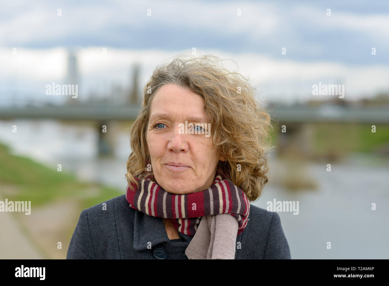Smiling attractive woman with tousled curly hair wearing a warm winter coat and scarf posing outdoors on a grey day near a river - Stock Image