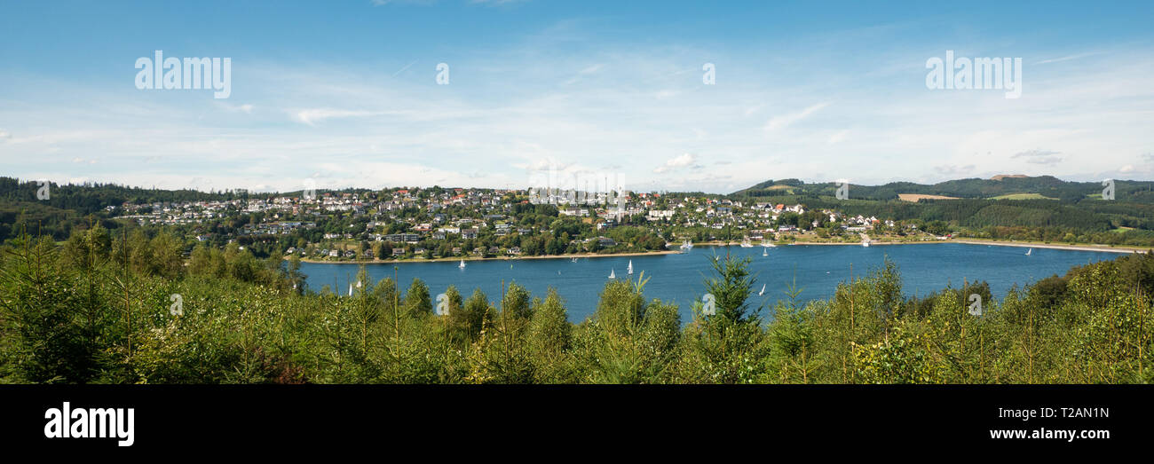 Wide view over Lake Sorpesee with sailboats and the dam with Langscheid in the background in front of a cloudy sky in Sundern, Sauerland, Germany Stock Photo