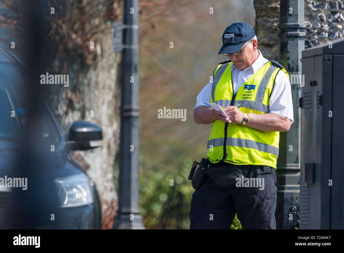 Male traffic warden from the council writing out a parking ticket in the UK. - Stock Image