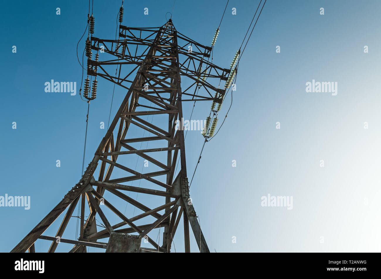 High voltage electricity pole on bright sky clouds background, electricity power transmission pylon - Stock Image