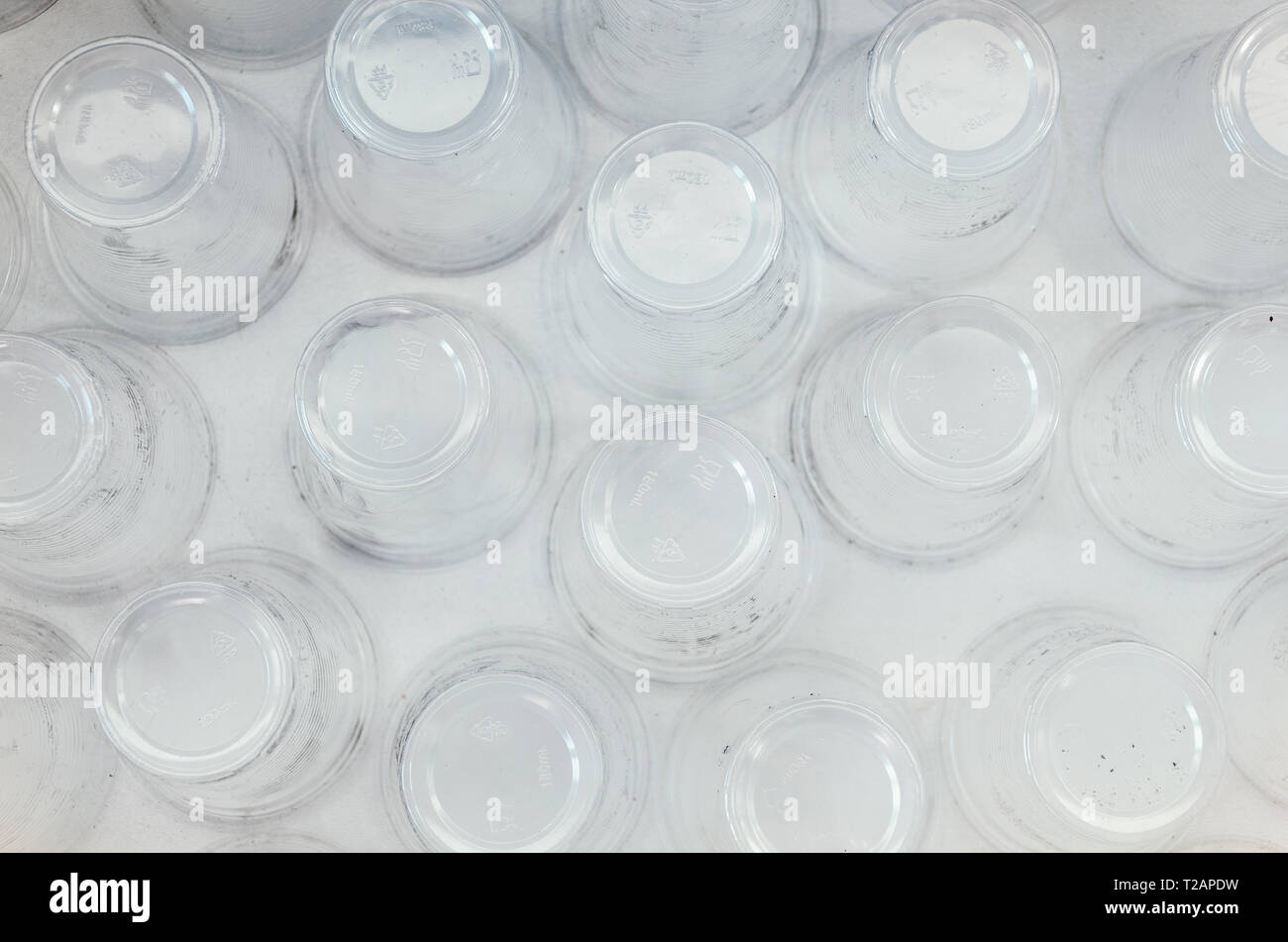 A lot of plastic cups, top view, white background. Increasing the amount of plastic concept. Non-compostable waste - Stock Image