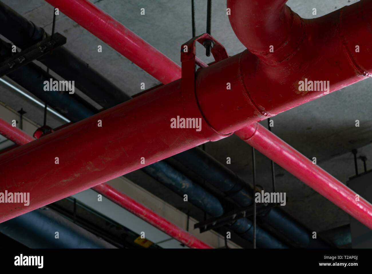 Fire sprinkler system with red pipes hanging from ceiling inside