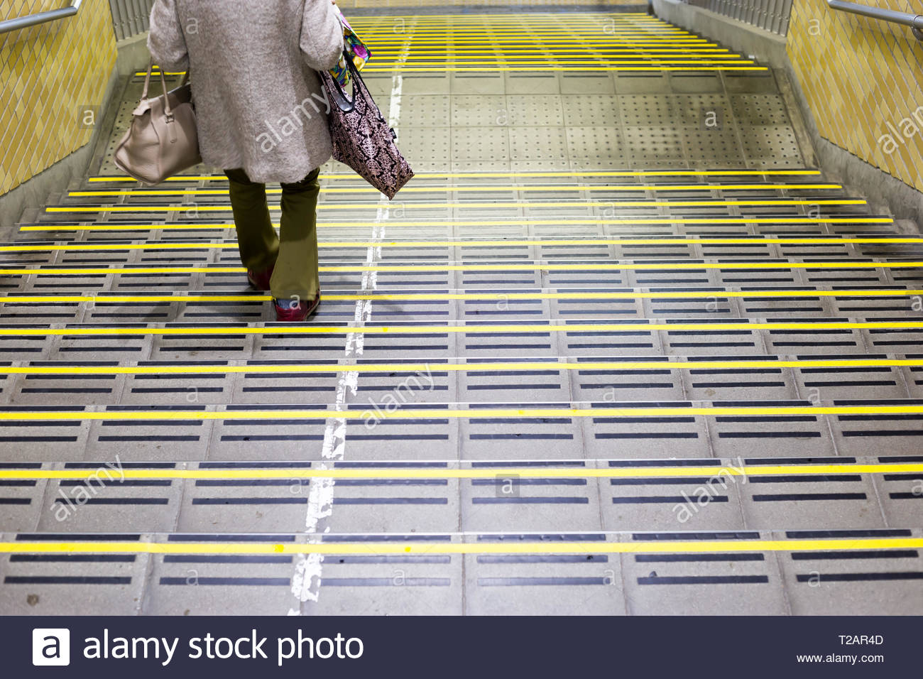 Chiba, Japan, 03/28/2019 , Stair of Chiba station, with a woman walking to the platform, at 5:30 am. - Stock Image
