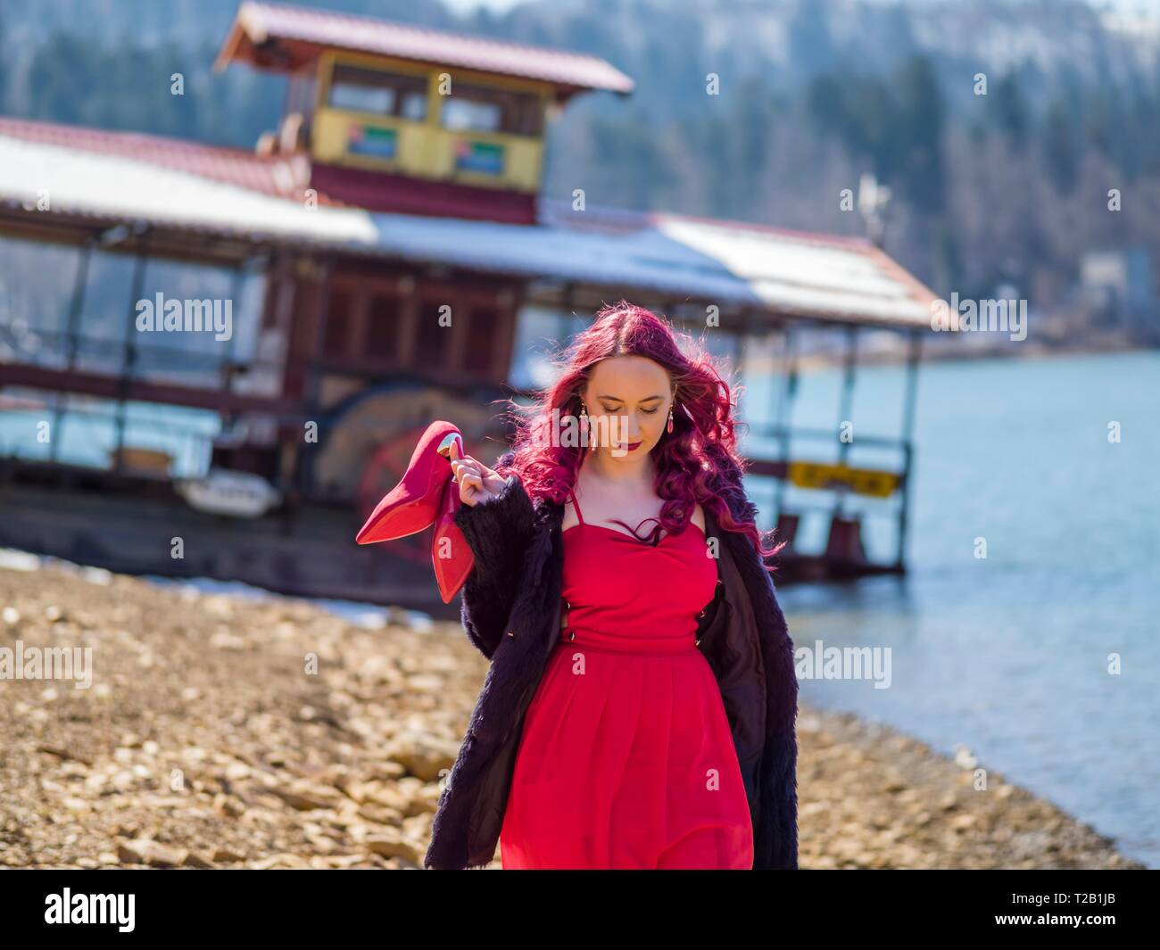 Young woman in 20s twenties outdoors in nature waking towards camera hand holding Red high-heeled heels stiletto shoes serious looking down - Stock Image
