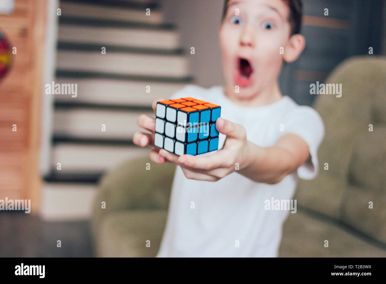 Yekaterinburg, Russia - March, 01, 2019. The boy is surprised and glad that he has completely collected Rubik's cube - Stock Image