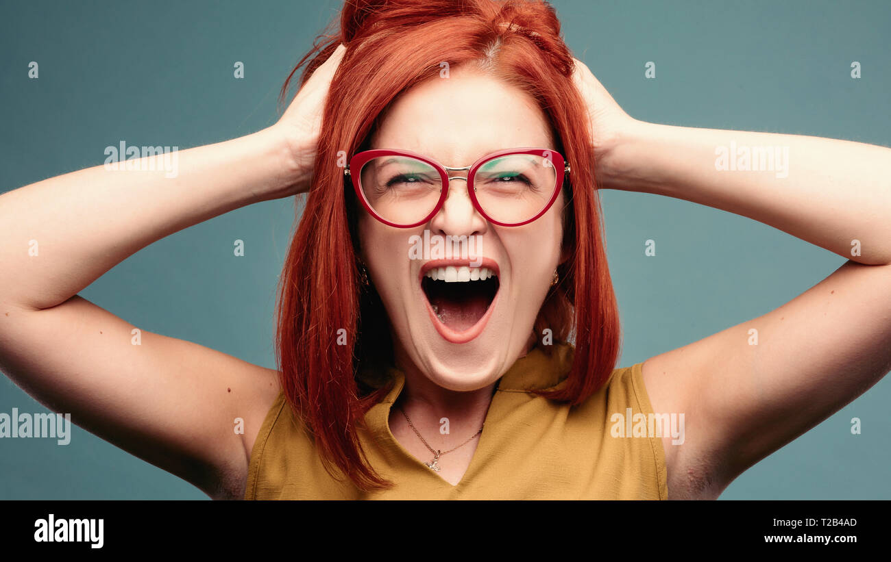 Happy and positivity red haired woman in eyeglasses shouting holding head by hands. - Stock Image