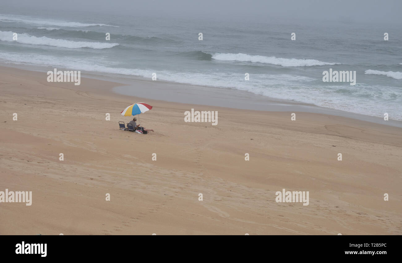 Beach with one single umbrella on a cloudy autumn day.  Desolate capture, with only couple visible under the umbrella Stock Photo