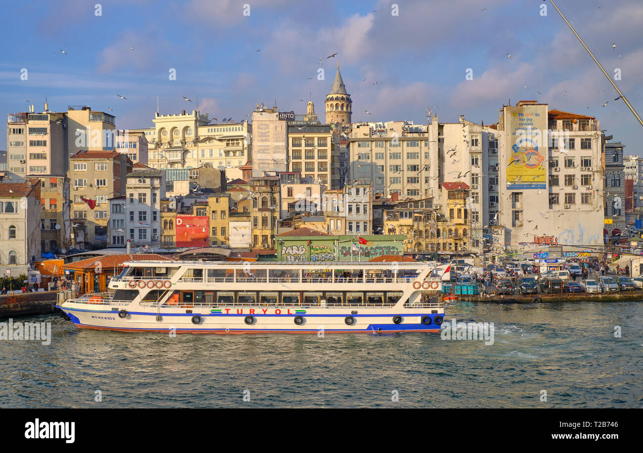 Ferry arriving at Karakoy (Turyol) station at bottom of Galata area.  View of river, and residential area in background, capture from Galata bridge.   Stock Photo
