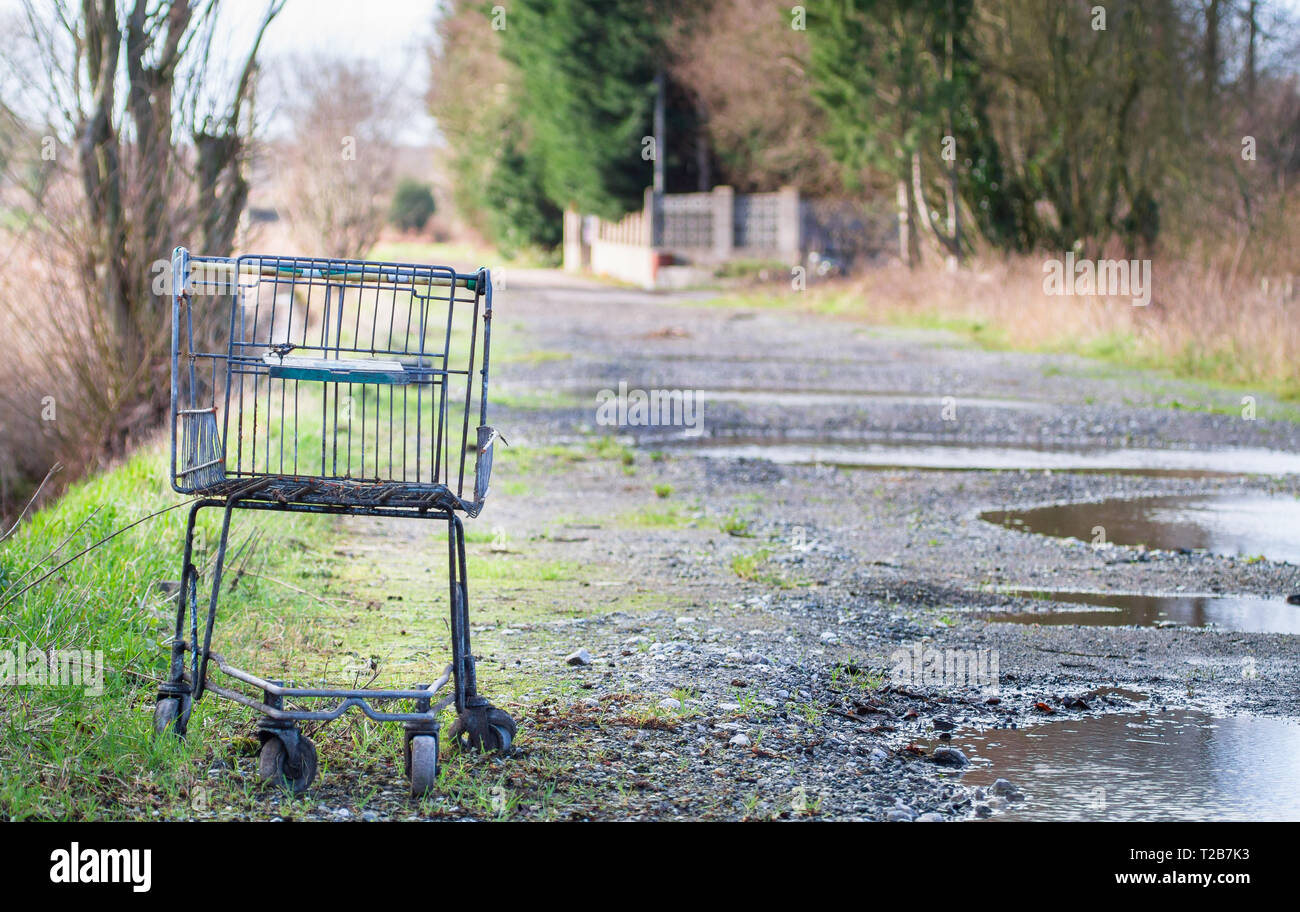 An old shopping cart/trolley sits on a gravel road outside the Furber's Scrapyard in Shropshire, England. - Stock Image