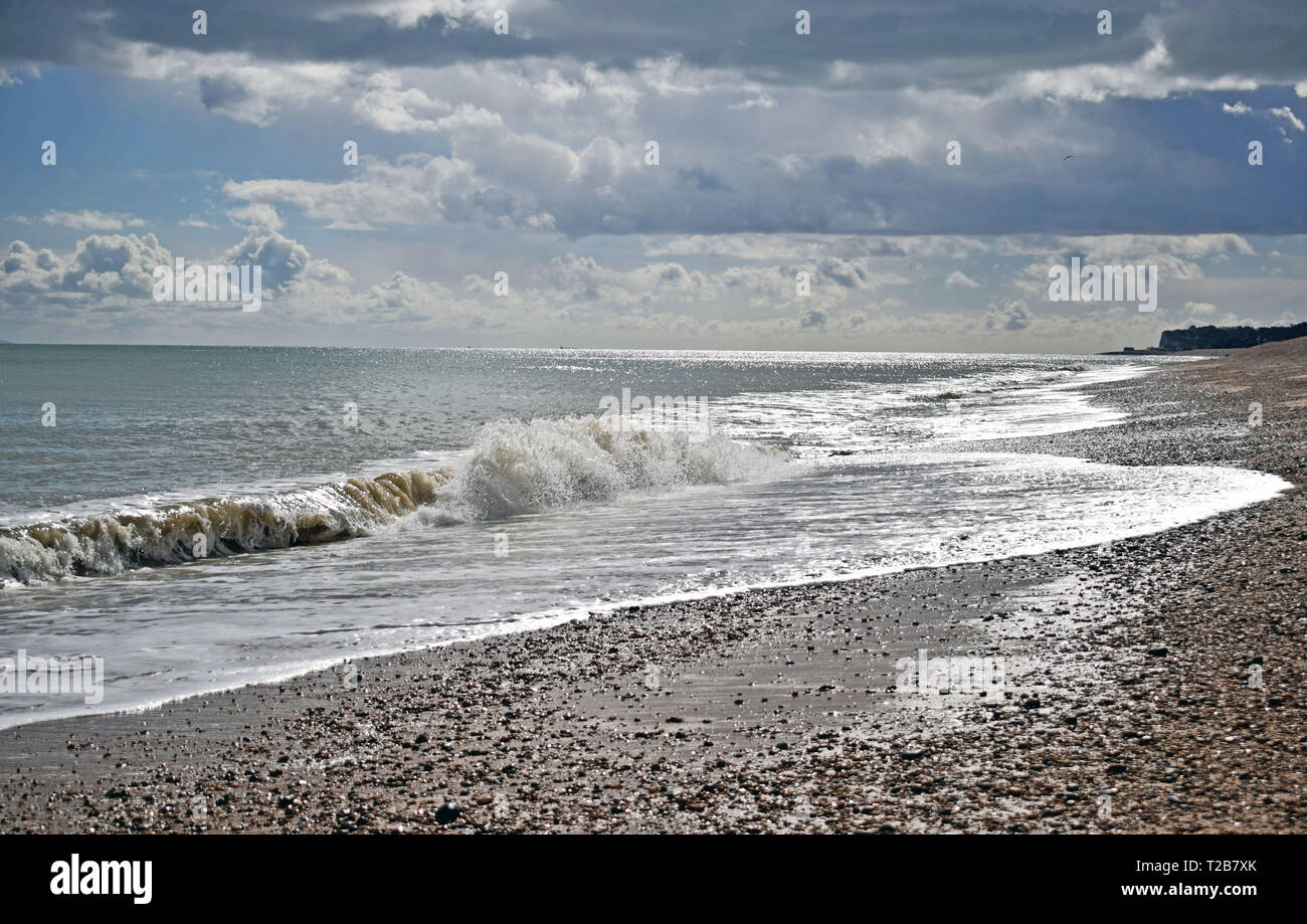Beautiful sea view of the rough waves breaking onto the pebble beach with a dramatic cloudy sky along the Kent coastline Stock Photo